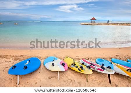 Surf boards on idyllic tropical sand Nusa Dua beach, Bali, Indonesia. - stock photo