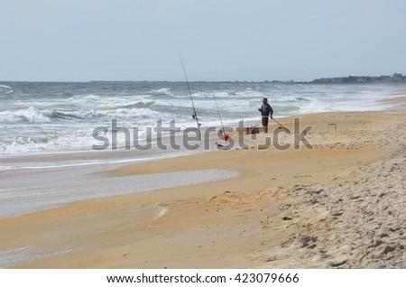 Surf Fisherman on the beach - stock photo