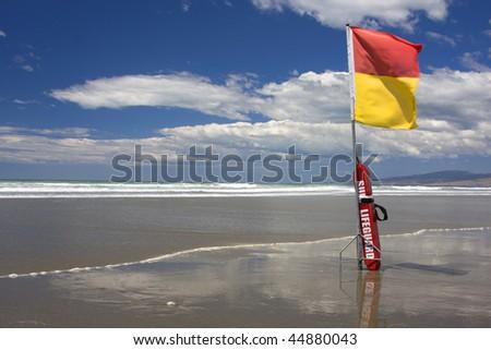 Surf Lifesaving flag and buoyancy aid on a New Zealand Beach - stock photo