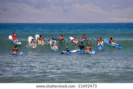 Surf school - several surfboarding students headed into an ocean swell - stock photo