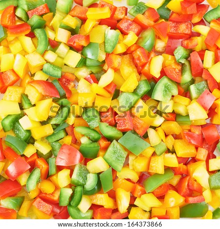 Surface coated with a sweet bell pepper cut into colorful pieces composition as an abstract food background - stock photo