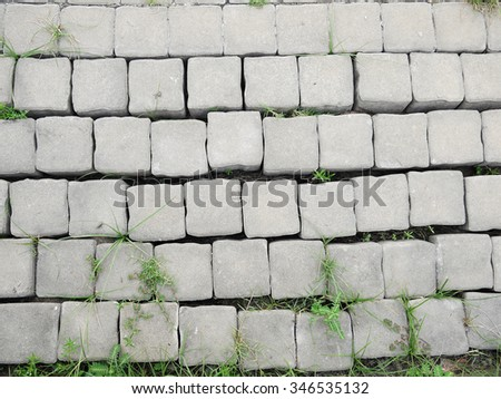 Surface of a broken cement brick pavement for textural background - stock photo