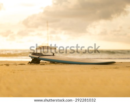 Surfboard on the beach at sunset in Thailand - stock photo