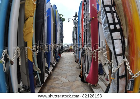 Surfboards lined up in the rack at famous Waikiki Beach. Oahu, Hawaii. - stock photo
