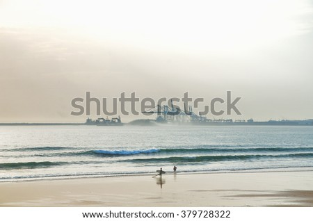 Surfer and peoples on the beach with industrial harbor on background - stock photo