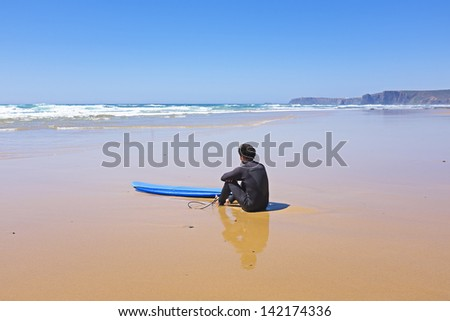Surfer at the beach watching the waves - stock photo