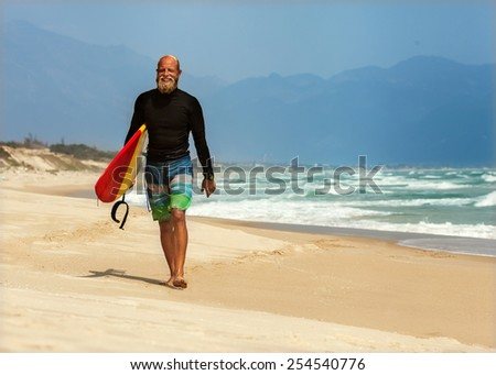 Surfer at the sea is standing with a surf board bright color. - stock photo