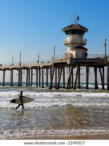 Surfer carries his surfboard at Huntington Beach Pier.
