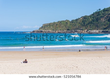Surfer do water sport, people relax at the beach La Zurriola in Donostia San Sebastian. The beach is situated at the district Gros of San Sebastian. The beach is famous for surfing