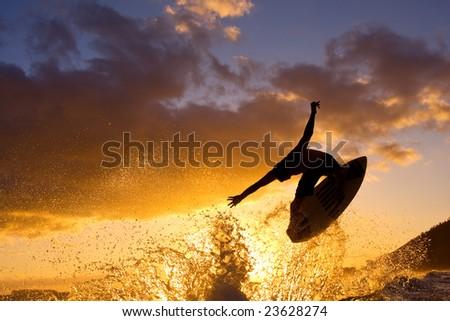 Surfer Does an Air at Sunset - stock photo