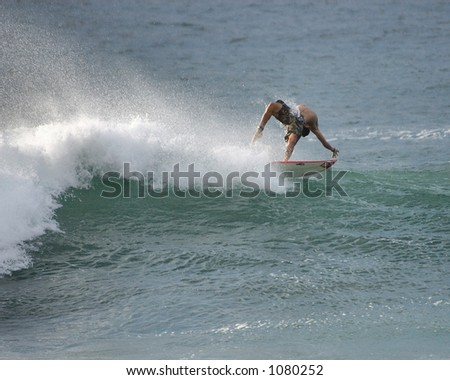 Surfer falls from a wave at Bonzai Pipeline off of Oahu's North Shore. (image contains noise) - stock photo