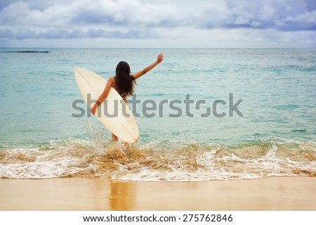 Surfer girl happy cheerful going surfing at ocean beach running into water. Female bikini woman heading for waves with surfboard having fun living healthy active lifestyle by sea. - stock photo