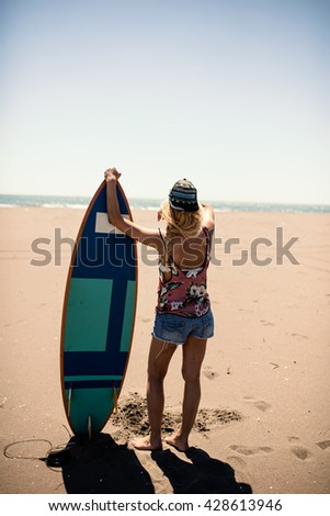 Surfer girl looking for the waves - stock photo