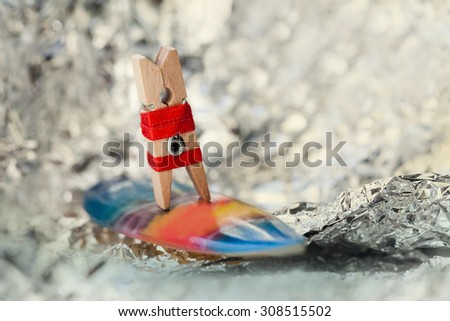 Surfer girl on a wave. Abstract sport concept with surfing clothespin. Soft focus background, toned photo. - stock photo