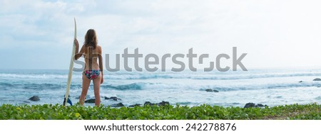 Surfer girl standing with board on the green beach - stock photo