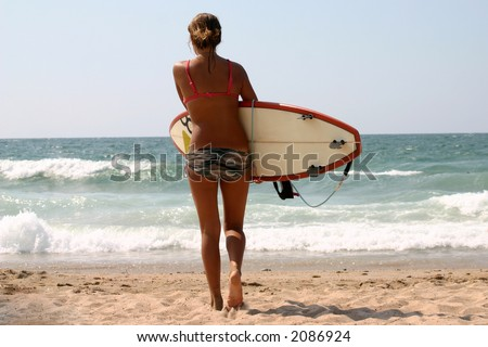 Surfer girl waiting the right moment to surf - stock photo