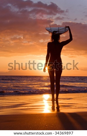 surfer girl with surfboard at sunset beach in maui hawaii - stock photo