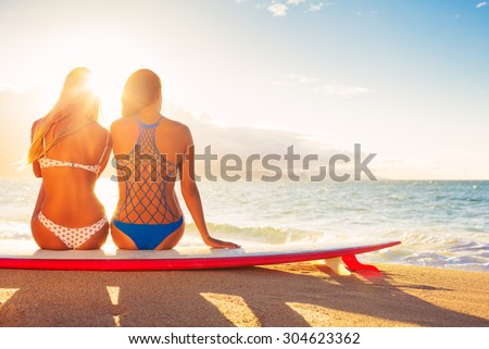 Surfer Girls on the Beach At Sunset. Summer Outdoor Lifestyle. Best Friends Hanging Out on the Beach.  - stock photo