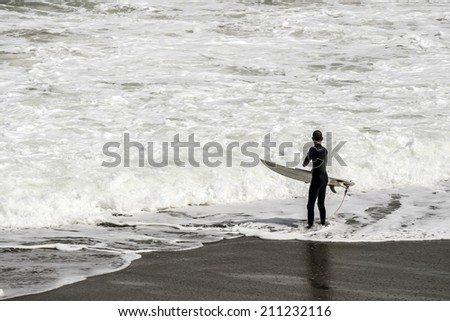 surfer go to the waves at the beach, - stock photo