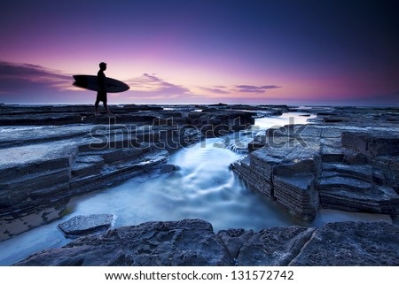 Surfer heading out in the morning light - stock photo