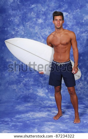 surfer holding a surfboard (studio photo) - stock photo
