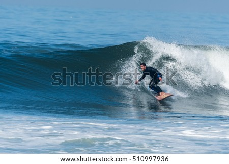 Surfer in action on the ocean waves on a sunny day.