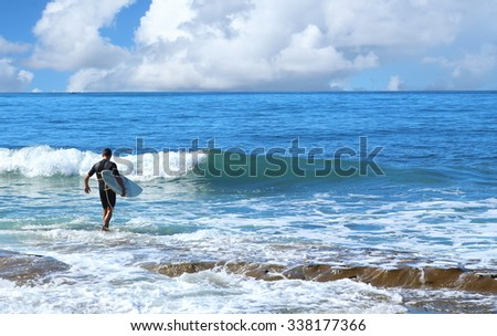 Surfer in black wet suit walking in to water on sunny day - stock photo