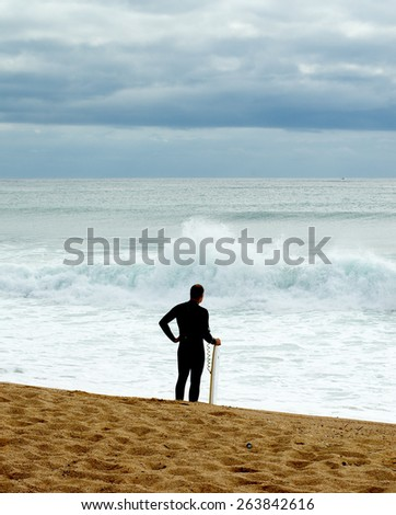 Surfer in Diving Suit Standing on Coastline and Waiting for Waves Outdoors - stock photo