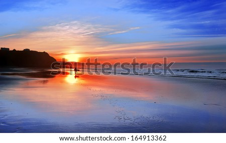 surfer in the beach at sunset with beautiful reflections - stock photo