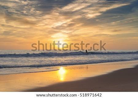 Surfer in the sea, on a background of the sunset rides.