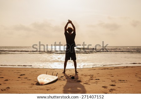 surfer man fitness stretching silhouette on beach - stock photo