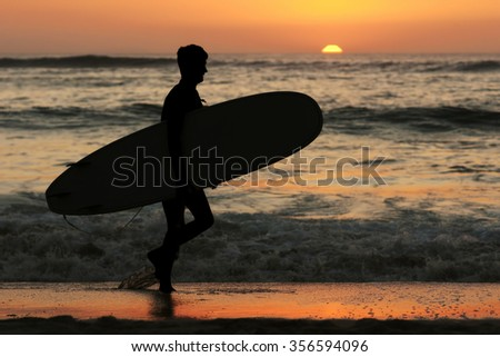 surfer men  in the beach shore silhouette  at sunset - stock photo