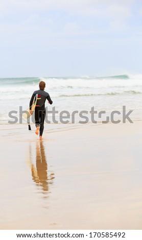 Surfer on a beach - stock photo