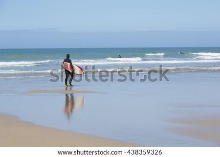 Surfer on a sandy beach - stock photo