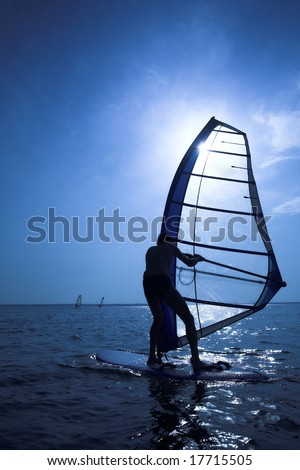 Surfer on sunset on waves - stock photo