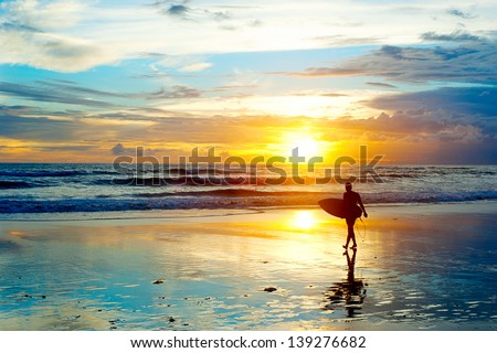 Surfer on the ocean beach at sunset on Bali island, Indonesia - stock photo