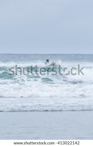 surfer paddling out over wave