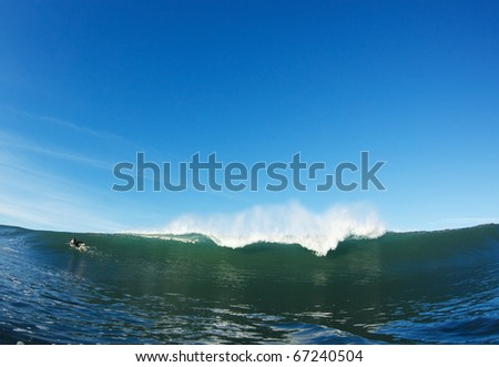 Surfer Paddling Over Ocean Wave, View from Water Level - stock photo