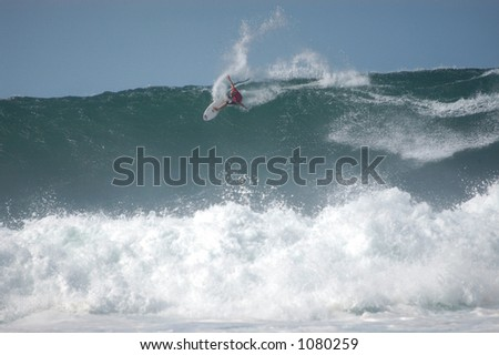 Surfer rides a wave at Bonzai Pipeline off of Oahu's North Shore. (image contains noise) - stock photo