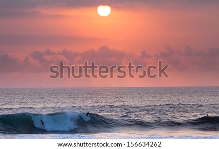 Surfer riding at sunset in Ocean Wave in Bali, Indonesia - stock photo