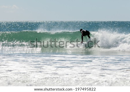 Surfer riding big ocean wave on surfboard as it starts to break with spray flying - stock photo
