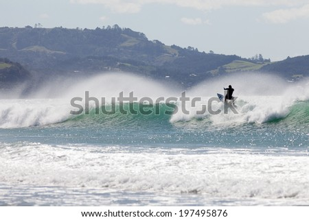Surfer riding the crest of big ocean wave on surfboard as it starts to break with spray flying - stock photo