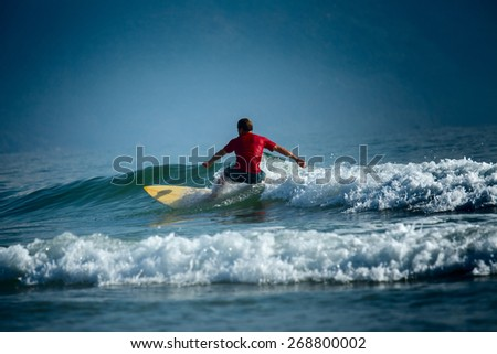 Surfer riding the wave on the short board at sunny day - stock photo