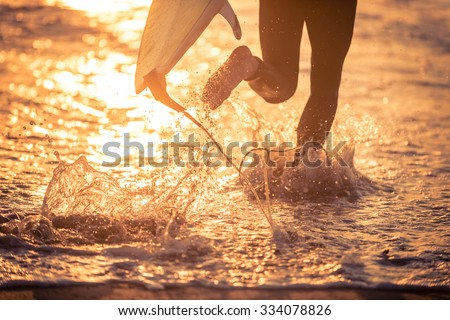 Surfer running in the water with his board. Ready for a great surfing day - stock photo