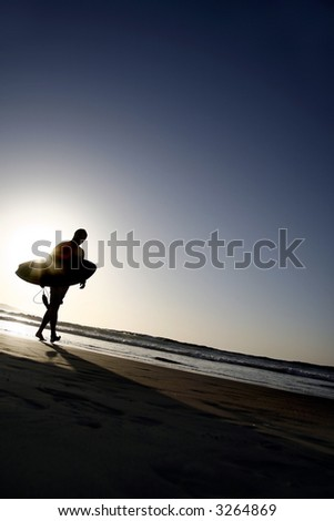 Surfer Silhouetted on an Empty Beach - stock photo