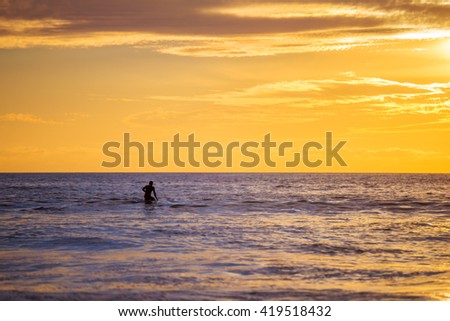 Surfer sits on their surfboard at sunset on the ocean. - stock photo