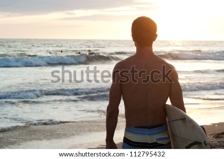 surfer sitting on the beach during sunset - stock photo