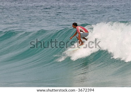 Surfer takes off on a clean tropical wave in Phuket, Thailand