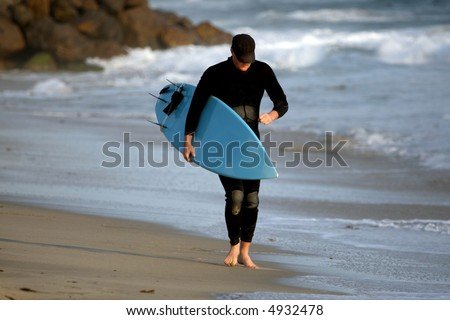 Surfer walking on the beach at sunset - stock photo