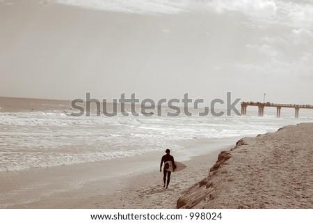 Surfer walking the beach toward pier - stock photo